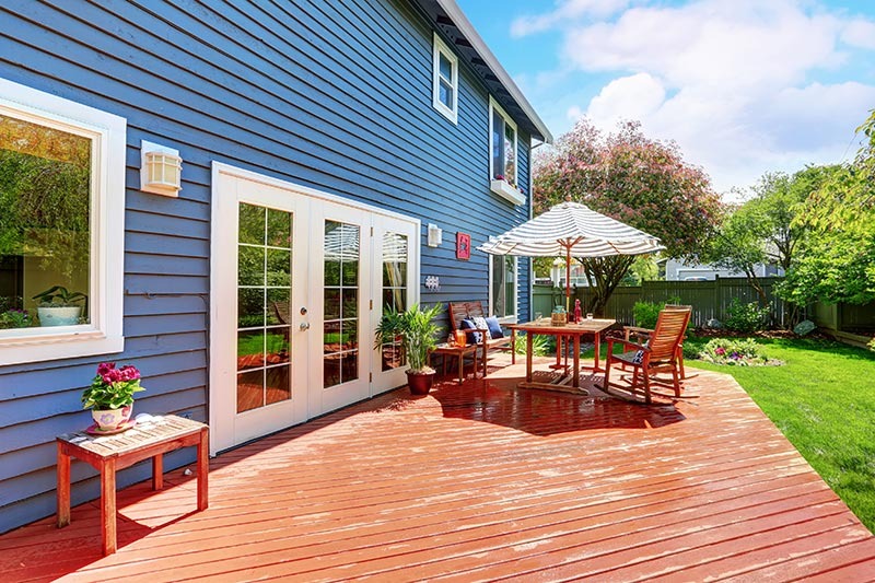 Blue vinyl siding on home with wooden patio in backyard