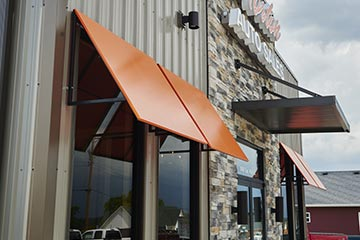Orange window awnings on the front of an auto store