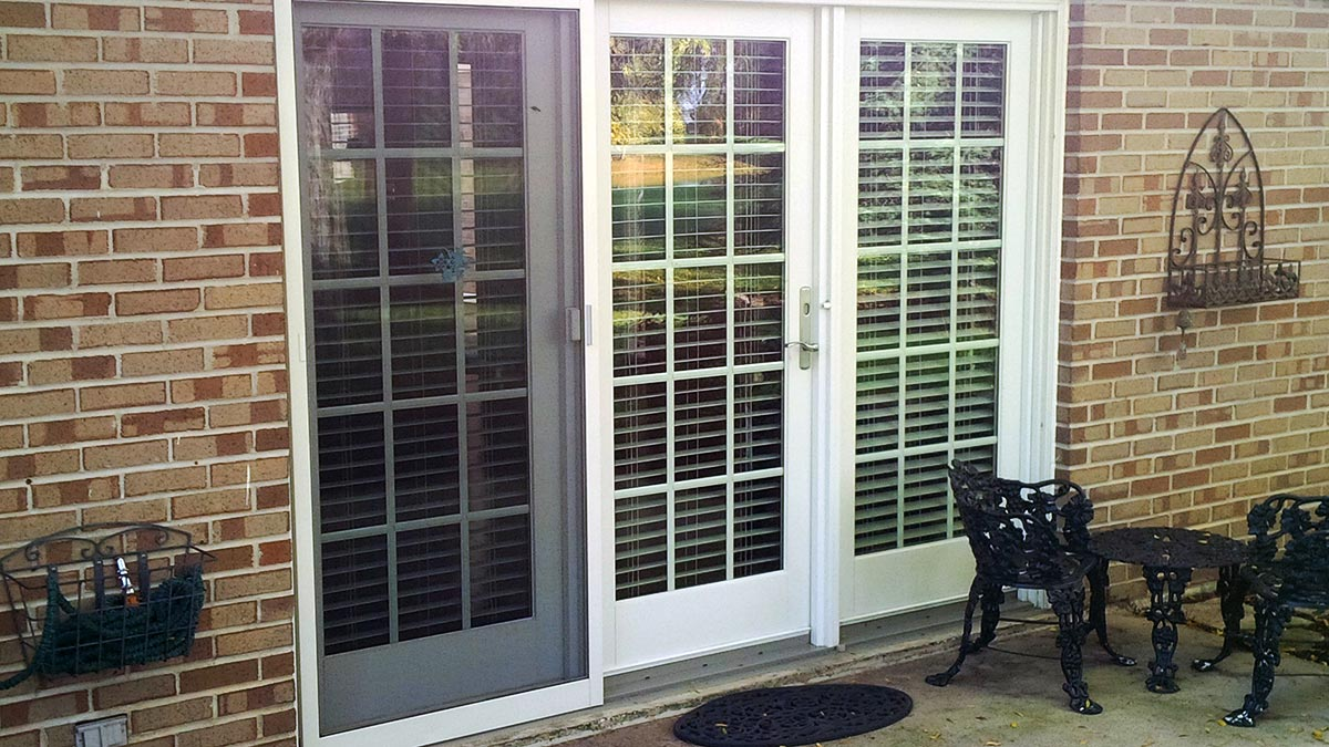 Three glass doors facing an exterior patio on a brick home