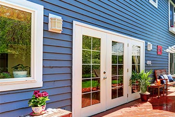 Exterior photo of blue house with siding featured