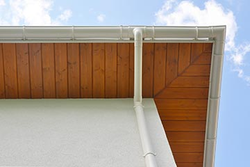 Wooden soffit overhanging side of house with gutters